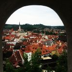 A photo of the tiny, family oriented town of Cesky Krumlov viewed from a peephole by their town's castle.