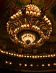 This grand chandelier hangs above the audience in the famed Opéra de Paris.
