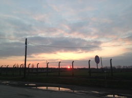 Sun setting over the electric fences surrounding Auschwitz